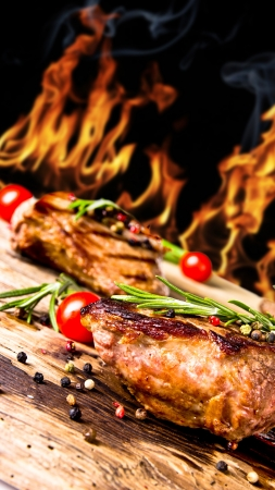 fire wood heat: Grilled beef steaks with flames on background
