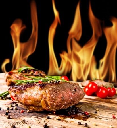 Grilled beef steaks with flames on background Stock Photo - 14006579