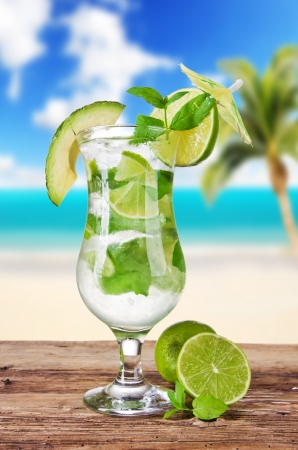 Mojito drink with blur beach on background photo