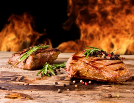 Grilled beef steaks with flames on background Stock Photo - 14389899
