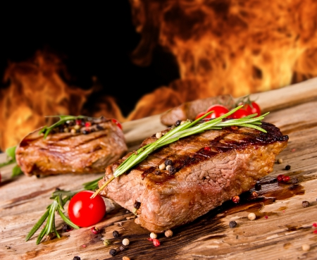 Grilled beef steaks with flames on background Stock Photo - 14389902