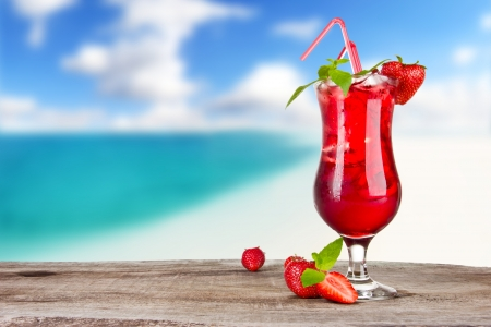 garnish: Strawberry cocktail with blur beach on background