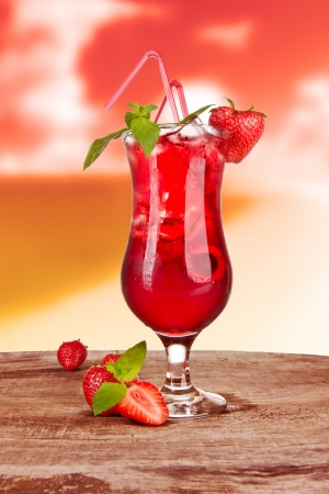 Strawberry cocktail in sunset with blur beach on background photo