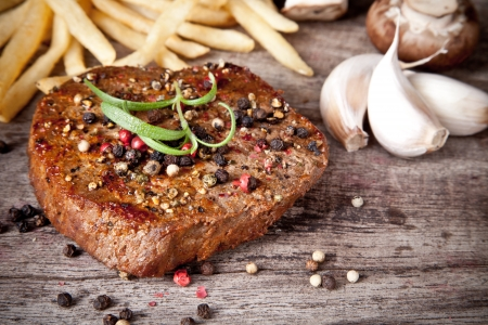 Delicious beef steak on wooden table photo