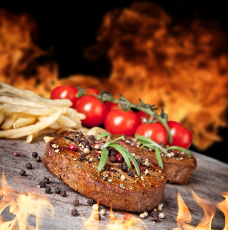 Delicious beef steaks with vegetable on wooden table photo