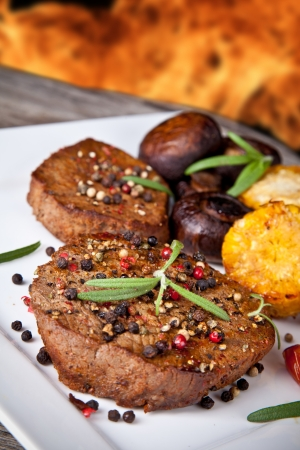 delicious grilled steak with vegetable on wooden table  photo