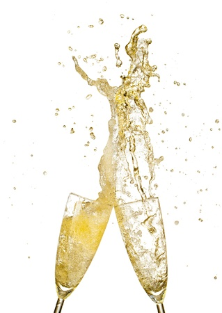 Splashing champagne out of glasses, concept of celebration  Isolated on white background photo