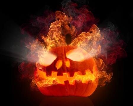 Burning halloween pumpkin, isolated on black background photo