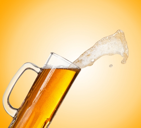 pouring beer: Beer splashing out of glass
