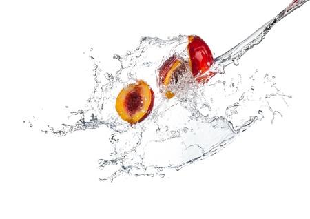 durazno: Nectarinas en salpicaduras de agua, aislados en fondo blanco