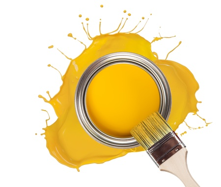 Yellow paint splashed out from can, isolated on white background photo