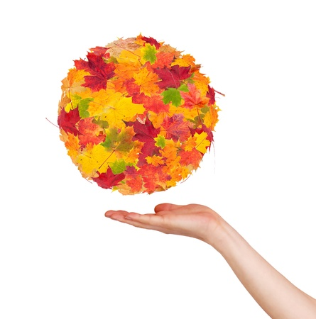 Woman hand holding autumn abstract ball, isolated on white background photo