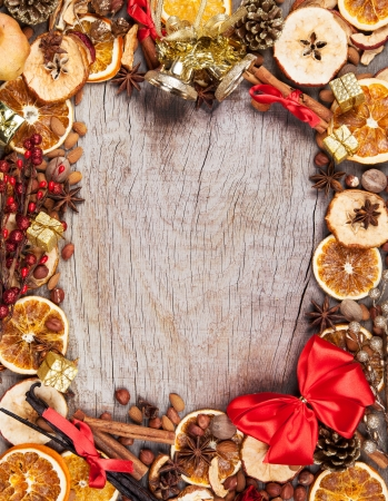 Christmas spices with dry orange and apple slices in frame with free space for text photo