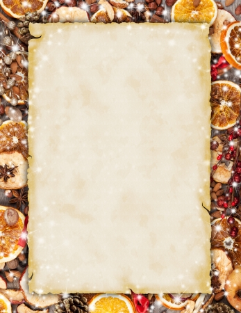 Christmas spices with dry orange and apple slices in frame with blank old paper photo
