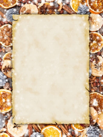badian: Christmas spices with dry orange and apple slices in frame with blank old paper