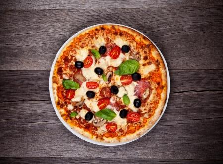 Heerlijke Italiaanse pizza geserveerd op houten tafel