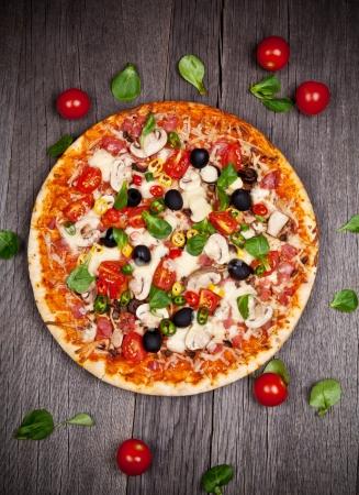 trompo de madera: Pizza italiana delicioso servido en la mesa de madera Foto de archivo