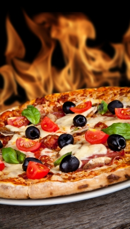 Delicious italian pizza served on wooden table with flames on background photo