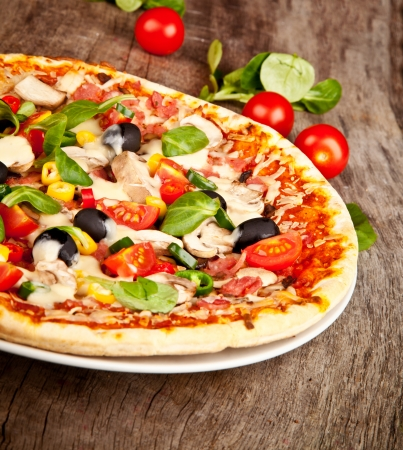 pizza ingredients: Delicious italian pizza served on wooden table