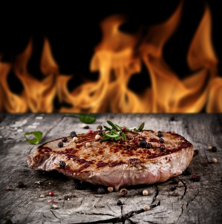 grilled steak: Delicious beef steak on wood with flames on backgrouns
