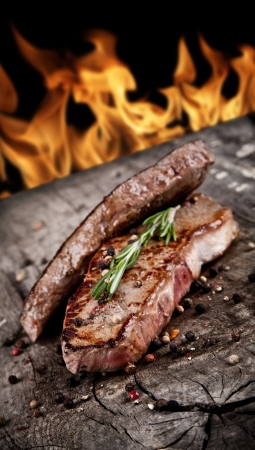 Delicious beef steaks on wood with flames on backgrouns photo