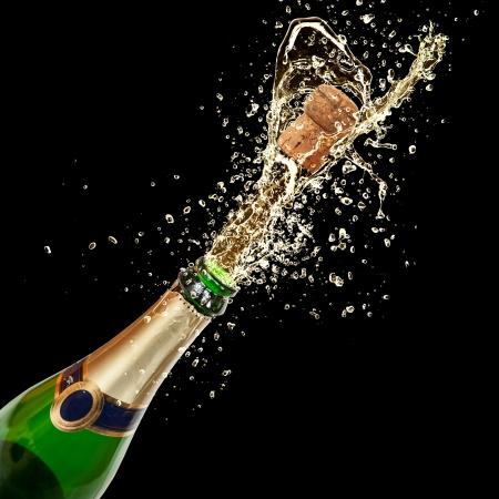 botella champagne: Celebración con champán tema salpicar, aislado sobre fondo negro