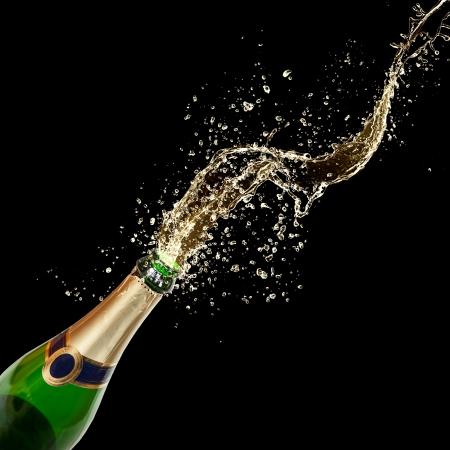 Celebration theme with splashing champagne, isolated on black background photo
