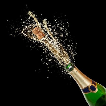 bouteille champagne: Thème Célébration avec le champagne éclaboussures, isolé sur fond noir