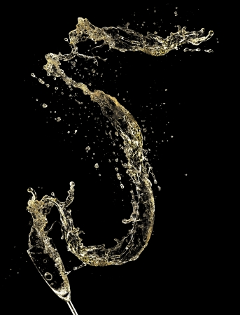 Celebration theme with splashing champagne, isolated on black background photo