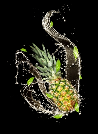 Pine-apple in water splash, isolated on black background photo