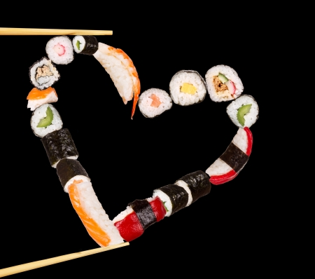 Sushi sticks holding pieces of sushi in heart shape, isolated on black background