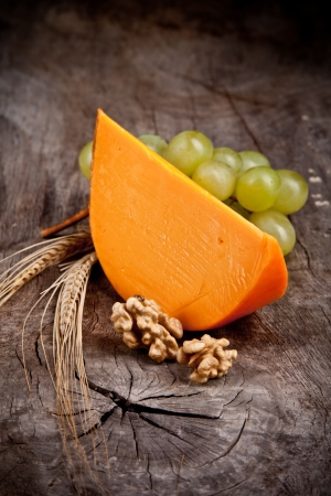 Delicious french yellow cheese on wooden table photo
