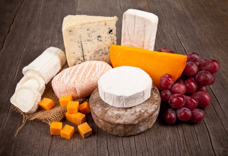 Delicious fresh french cheeses served on wooden table photo