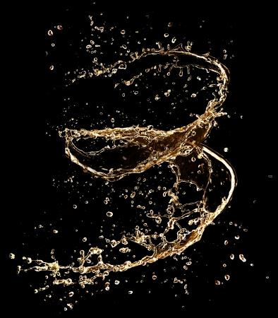 abstract liquor:  Champagne splash isolated on black background  Stock Photo