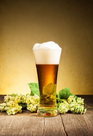 Glass of beer on wooden table photo