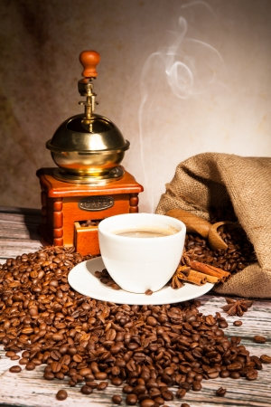 Coffee still life with wooden grinder and cup photo