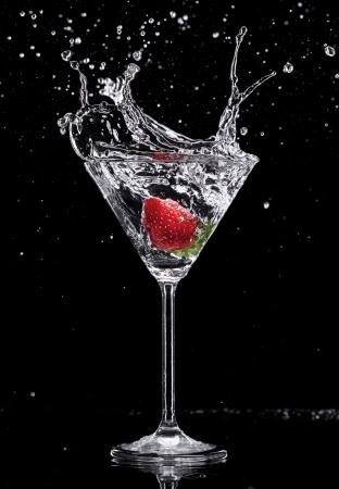 copa de martini: Bebida de Martini que salpica hacia fuera del vidrio, aislado en fondo negro
