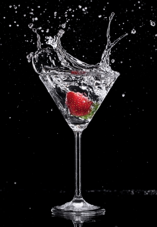 martini glass: Martini drink splashing out of glass, isolated on black background