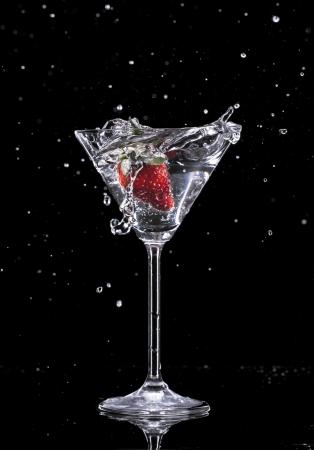martini splash: Martini drink splashing out of glass, isolated on black background