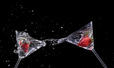 Martini drinks splashing out of glass, isolated on black background photo