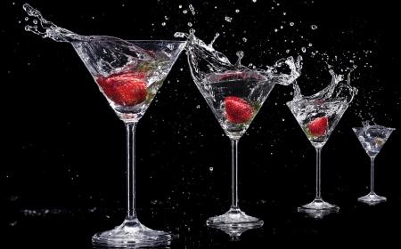 Martini drinks with splashes, isolated on black background