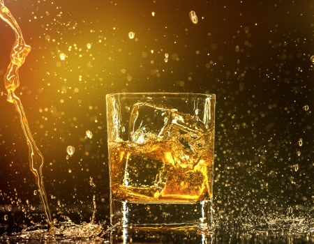 whiskey glass: Whiskey splashing around glass Stock Photo