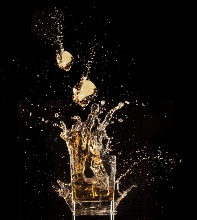 spatter:  Glass of whiskey with splash, isolated on black background Stock Photo