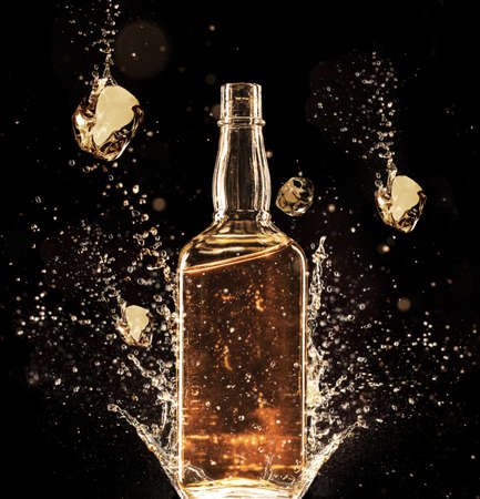 botella de whisky: Concepto de que se derrame líquido alrededor de la botella, aislado en fondo negro Foto de archivo