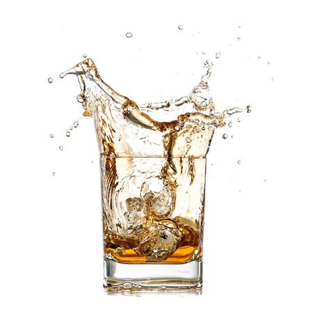 scotch whisky: Whiskey splashing out of glass, isolated on white background