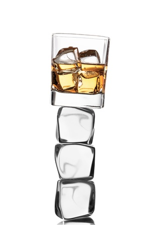 Whiskey glass on ice cubes, isolated on white background photo