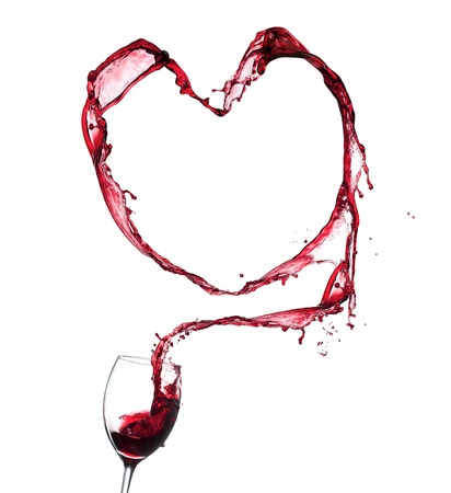 Red wine splashing from glass in heart shape, isolated on white background photo