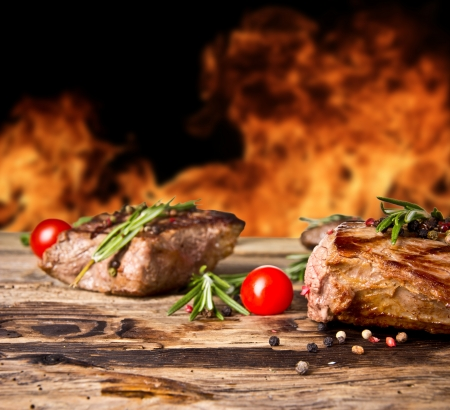 grill food: Grilled beef steaks with flames on background