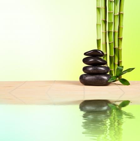 steine im wasser: Spa Stilleben mit Lavasteinen und Bambussprossen mit freiem Platz f�r Text