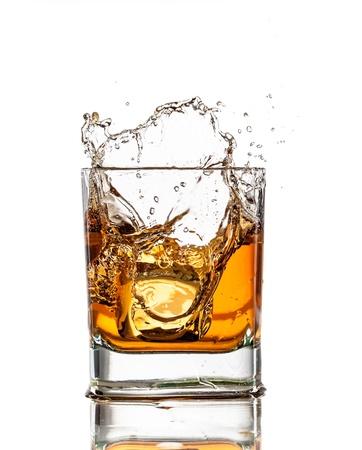 bebidas alcoh�licas: Whisky vidrio con salpicaduras, aislados en fondo blanco